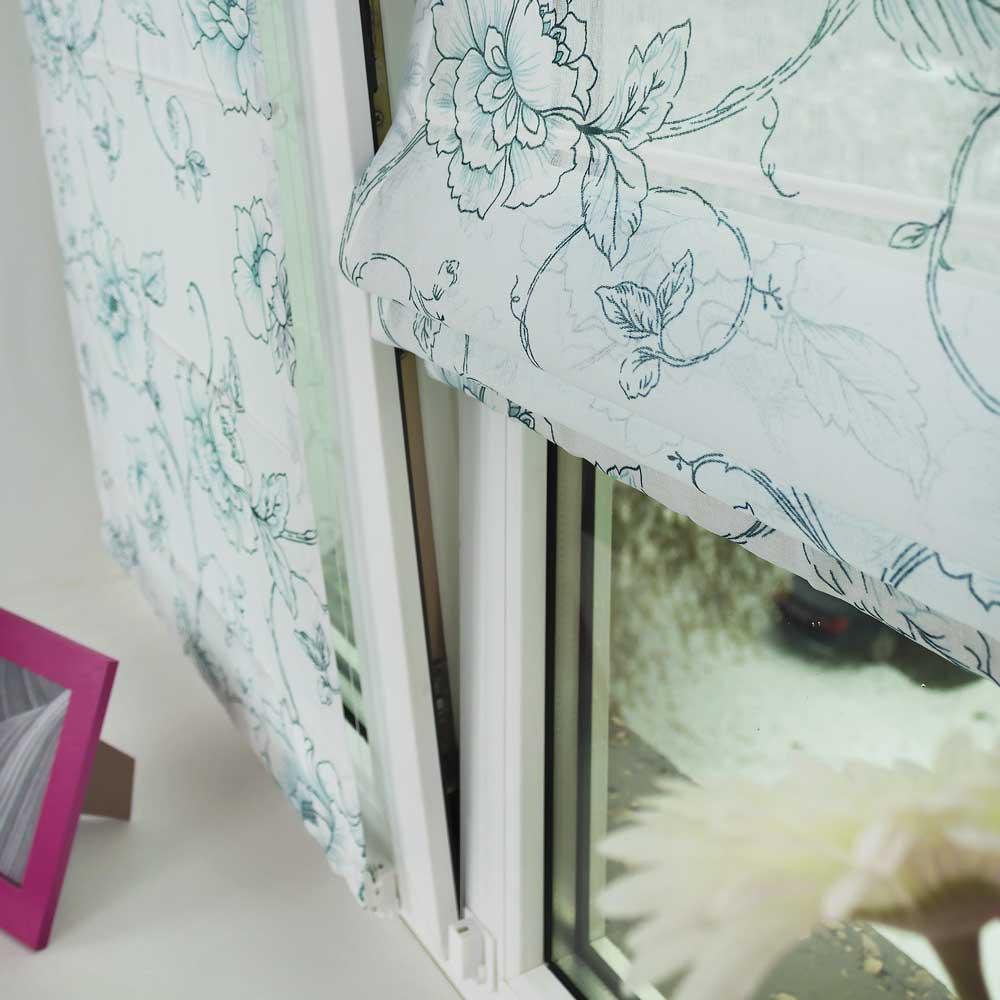 Мини римская штора из легкой ткани удерживается на открытом окне струнным механизмом.