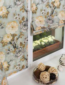 Мини римские шторы на пластиковом окне. Шторы выполнены из ткани с цветочным рисунком в голубых тонах