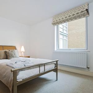 Римская штора из ткани с орнаментом на сером фоне в спальне