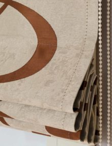 Римские шторы бежевого цвета собираются в складки с помощью цепочки